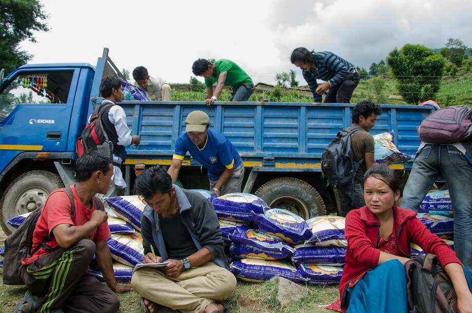 Villagers unload the supply truck from Kathmandu at the end of the road in Bothang. The truck contains two months worth of supplies for 187 families. Photo: Nat Needham, Special To The Chronicle