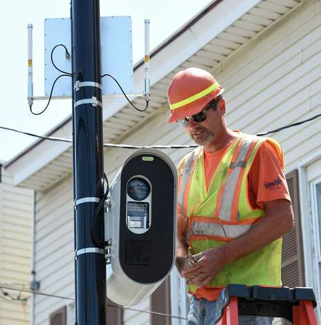 Jeff Smith of the Stilsing Company puts the finishing touches on a red-light camera that looks in to the intersection of Quail Street and Washington Avenue Thursday afternoon, July 16, 2015, in Albany, N.Y. Two intersections selected to receive red light cameras in the city of Albany will be going live on Monday morning after midnight. (Skip Dickstein/Times Union) Photo: SKIP DICKSTEIN / 00032626A