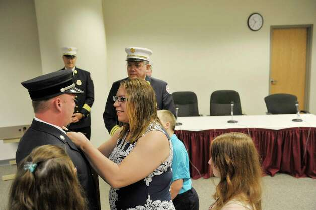 Firefighter Dennis Laranjo's wife, Alayna Laranjo pins the captain's badge on him as their children look on during a promotions ceremony at Troy City Hall on Thursday, July 16, 2015, in Troy, N.Y. Firefighter Dennis Laranjo was promoted from lieutenant to captain and firefighter Thomas Miter was promoted from captain to battalion chief.   (Paul Buckowski / Times Union) Photo: PAUL BUCKOWSKI / 00032645A
