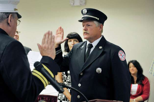Firefighter Thomas Miter, right, is given the oath from Troy Fire Chief Thomas Garrett, as Miter's wife, Sheri Miter, looks on during a promotions ceremony at Troy City Hall on Thursday, July 16, 2015, in Troy, N.Y. Firefighter Dennis Laranjo was promoted from lieutenant to captain and firefighter Thomas Miter was promoted from captain to battalion chief.  (Paul Buckowski / Times Union) Photo: PAUL BUCKOWSKI / 00032645A
