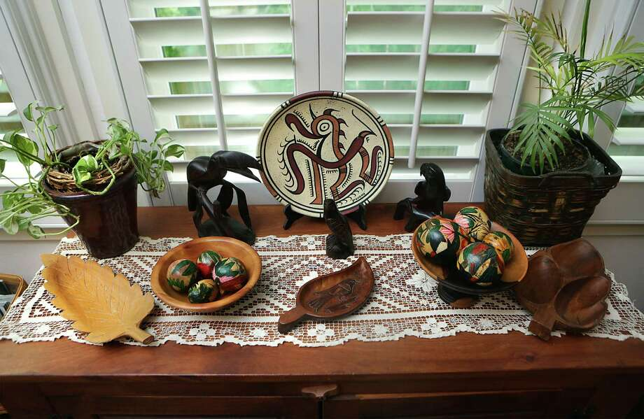 Panamanian wood carvings and painted gourds set on heirloom lace decorate a buffet in the kitchen of Glenda Kochel. Photo: Bob Owen /San Antonio Express-News / San Antonio Express-News