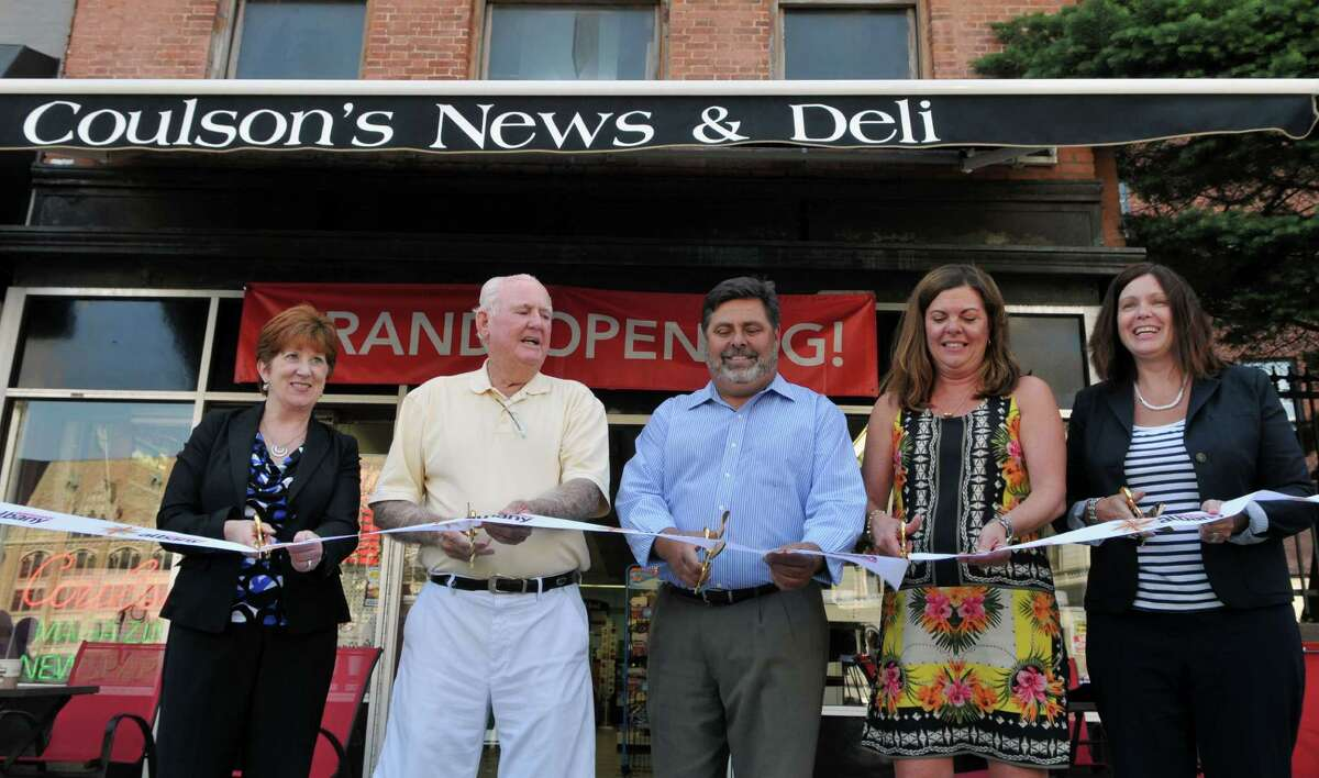 Mayor Kathy Sheehan, left, Richard Eustace, Richard Metzger, Tracy Metzger and Georgette Steffens cut the ribbon during the opening of a new deli counter at Coulson's News & Deli Thursday, July 16, 2015, in Albany, N.Y. Richard Metzger bought Coulson's in 2014 and recently sold it to Diana Ortiz and Steve Colon. (Phoebe Sheehan/Special to The Times Union)