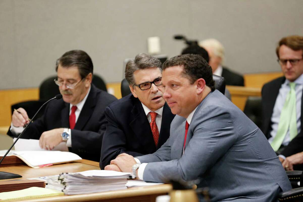 Texas Governor Rick Perry appears in Travis County Court on Thursday to answer charges in an indictment regarding his veto of funding for the Travis County Public Integrity Unit. He speaks with defense lawyer Tony Buzbee as a second attorney David Botsford is on the left.