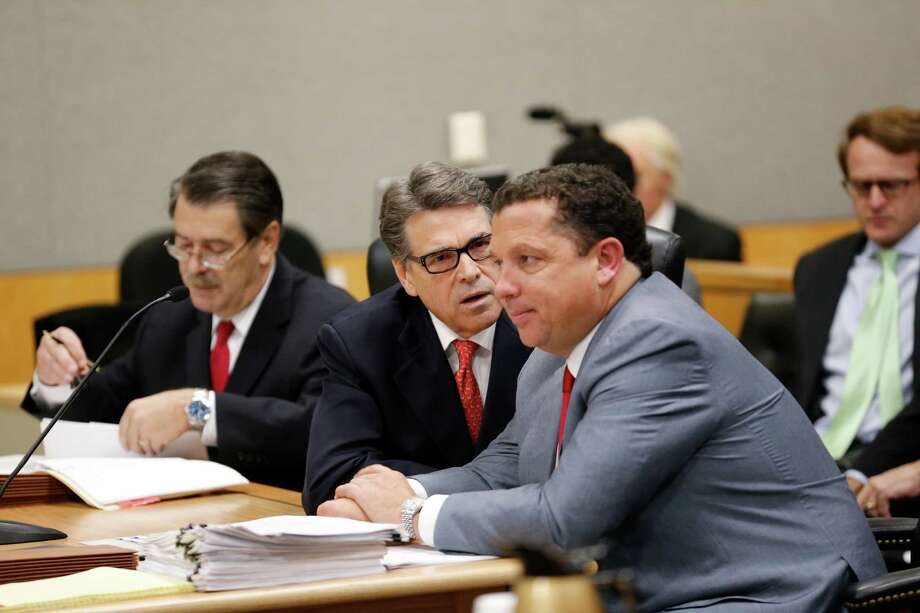 Texas Governor Rick Perry appears in Travis County Court on Thursday to answer charges in an indictment regarding his veto of funding for the Travis County Public Integrity Unit. He speaks with defense lawyer Tony Buzbee as a second attorney David Botsford is on the left. Photo: Bob Daemmrich, Photojournalist / Bob Daemmrich Photography, Inc.