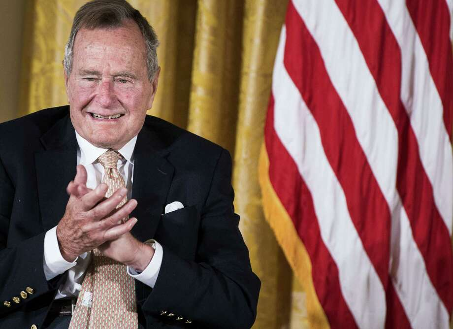 "(FILES) This July 15, 2013 file photo shows former US President George H. W. Bush as he applauds during an event in the East Room of the White House in Washington, DC. US ex-president George H.W. Bush fell and broke a bone in his neck July 15, 2015, his spokesman said, following reports that the former leader had been hospitalized yet again. ""His condition is stable -- he is fine -- but he'll be in a neck brace,"" Bush spokesman Jim McGrath tweeted. The 91-year-old former president, who fell Wednesday morning in Kennebunkport, Maine, was being treated at a hospital in the city of Portland some 30 miles (50 kilometers away), CNN reported.  ""We are not expecting a long stay,"" McGrath told the channel. AFP PHOTO/Brendan SMIALOWSKIBRENDAN SMIALOWSKI/AFP/Getty Images Photo: BRENDAN SMIALOWSKI, Staff / AFP"