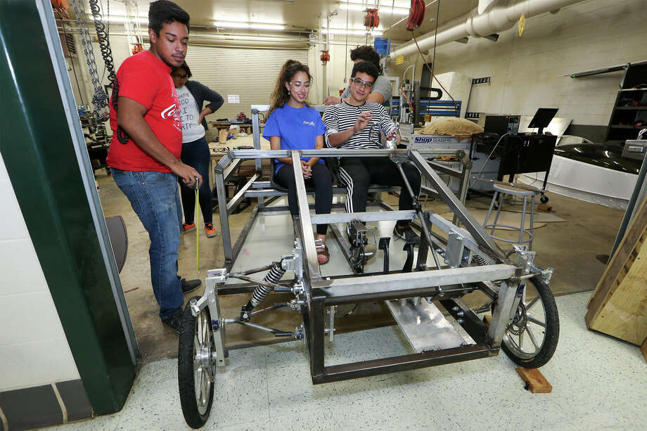 Alan Melecio, 18, and Natalie Sahagun, 17, sit in their team's solar-powered car as Jose Carlos, 18, looks on at Southwest High School. Photo: Marvin Pfeiffer /San Antonio Express-News / Express-News 2015