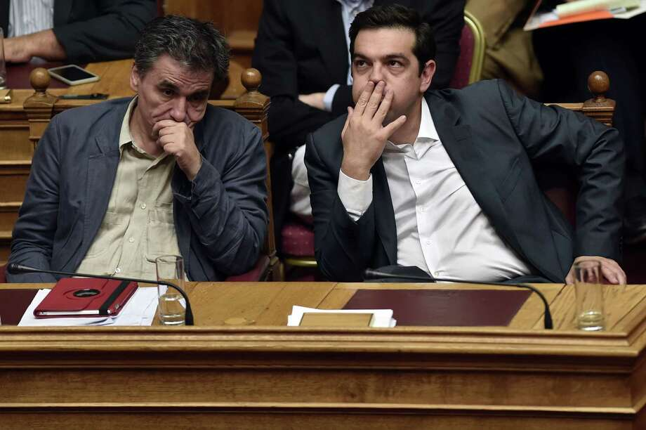 TOPSHOTS Greek Prime Minister Alexis Tsipras (R) and Finance Minister Eyclid Tsakalotos react during a parliament session in Athens on July 15, 2015. AFP PHOTO / ARIS MESSINISARIS MESSINIS/AFP/Getty Images Photo: ARIS MESSINIS, Staff / AFP / Getty Images / AFP