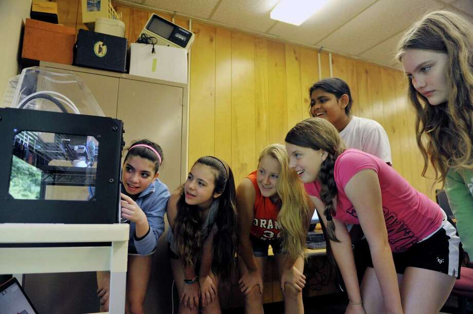 Students, from left to right, Gabriella Insero, 12, Christina Oberting, 12, Savannah Scoons, 13, Athena Rodrigues, 12, Alyssa Snyder, 12, and Zoe Zubrick, 13, look over a 3D printer as it prints one of their designs during 3D Printing and Technology Camp at the Academy of the Holy Names on Thursday, July 16, 2015, in Albany, N.Y. Students in the camp learned to design 3D objects and worked with a 3D printer on loan from RPI. They worked with simple circuits and LEDs and they built and programed Lego robot kits, on loan from the SUNY Polytechnic Institute. Donna Mooney, coordinator of science research and a physics teacher at the school and Elizabeth Vanderhoef, a 2007 graduate of Academy of the Holy Names and a high school physics teacher in Holland Patent, N.Y. said that they plan to hold the technology camp for girls next summer.  (Paul Buckowski / Times Union) Photo: PAUL BUCKOWSKI / 00032641A