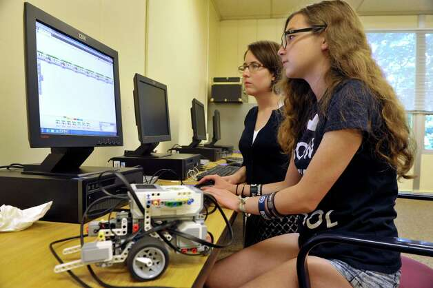 Kate Carbone, foreground,14, works with Elizabeth Vanderhoef, a 2007 graduate of Academy of the Holy Names and a high school physics teacher in Holland Patent, N.Y. as Carbone programs a Lego robot at the 3D Printing and Technology Camp at the Academy of the Holy Names on Thursday, July 16, 2015, in Albany, N.Y. Students in the camp learned to design 3D objects and worked with a 3D printer on loan from RPI. They worked with simple circuits and LEDs and they built and programed Lego robot kits, on loan from the SUNY Polytechnic Institute. Donna Mooney, coordinator of science research and a physics teacher at the school and Elizabeth Vanderhoef said that they plan to hold the technology camp for girls next summer.  (Paul Buckowski / Times Union) Photo: PAUL BUCKOWSKI / 00032641A
