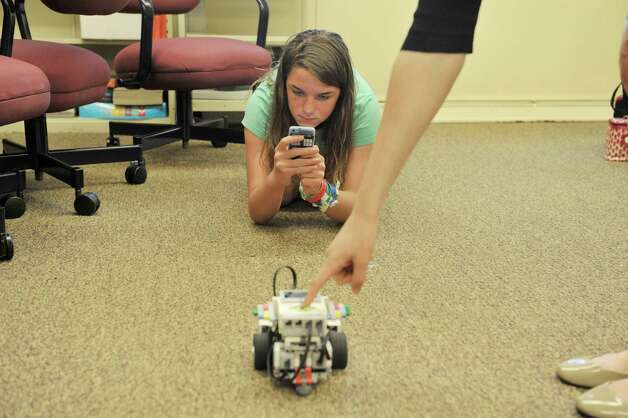 Emma Meyers, 13, films a Lego robot, that she and another girl programed to perform certain tasks at the 3D Printing and Technology Camp at the Academy of the Holy Names on Thursday, July 16, 2015, in Albany, N.Y. Students in the camp learned to design 3D objects and worked with a 3D printer on loan from RPI. They worked with simple circuits and LEDs and they built and programed Lego robot kits, on loan from the SUNY Polytechnic Institute. Donna Mooney, coordinator of science research and a physics teacher at the school and Elizabeth Vanderhoef, a 2007 graduate of Academy of the Holy Names and a high school physics teacher in Holland Patent, N.Y. said that they plan to hold the technology camp for girls next summer.  (Paul Buckowski / Times Union) Photo: PAUL BUCKOWSKI / 00032641A