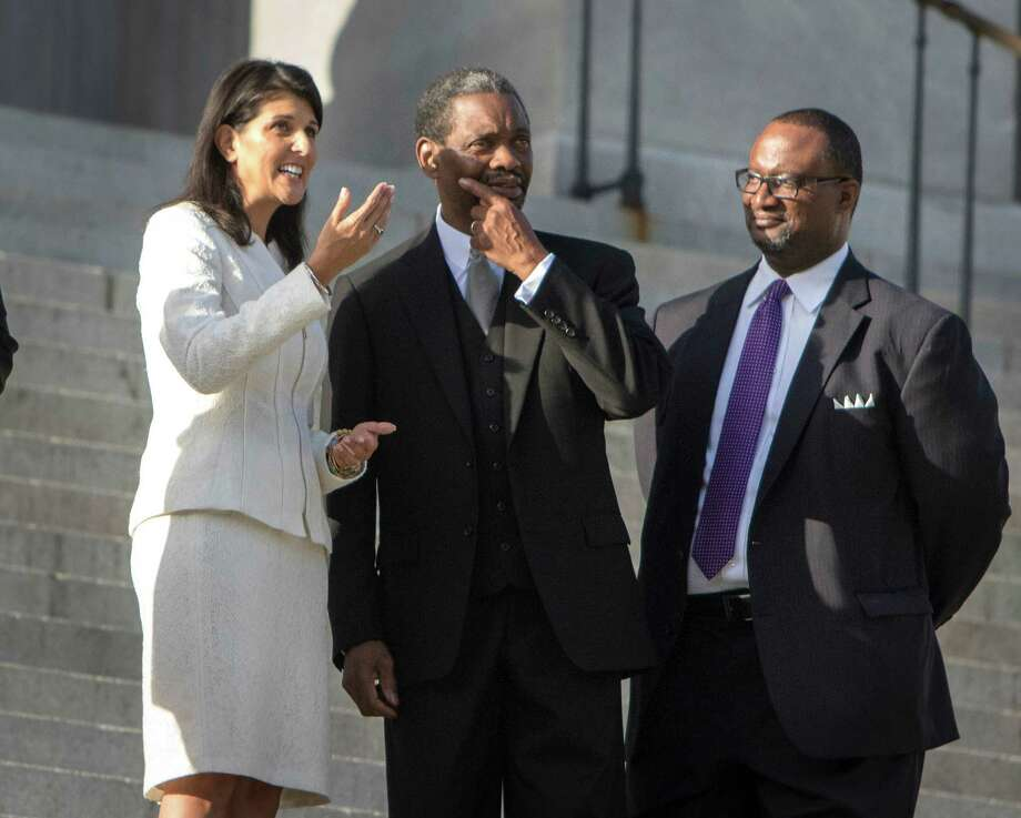 South Carolina Gov. Nikki Haley, left, talks interim pastor of Emanuel A.M.E. Church, the Rev. Norvel Goff, center, before officials remove the Confederate battle flag from Capitol grounds in Columbia, S.C. Haley is focused on community healing and moving forward. Photo: STEPHEN B. MORTON /New York Times / NYTNS