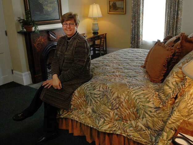 Kathleen Smith, owner of Saratoga Arms, a hotel located on Broadway in Saratoga Springs, NY, poses in one of the rooms at the hotel on Monday, April 19, 2010.    (Paul Buckowski / Times Union) Photo: PAUL BUCKOWSKI / 00008357A