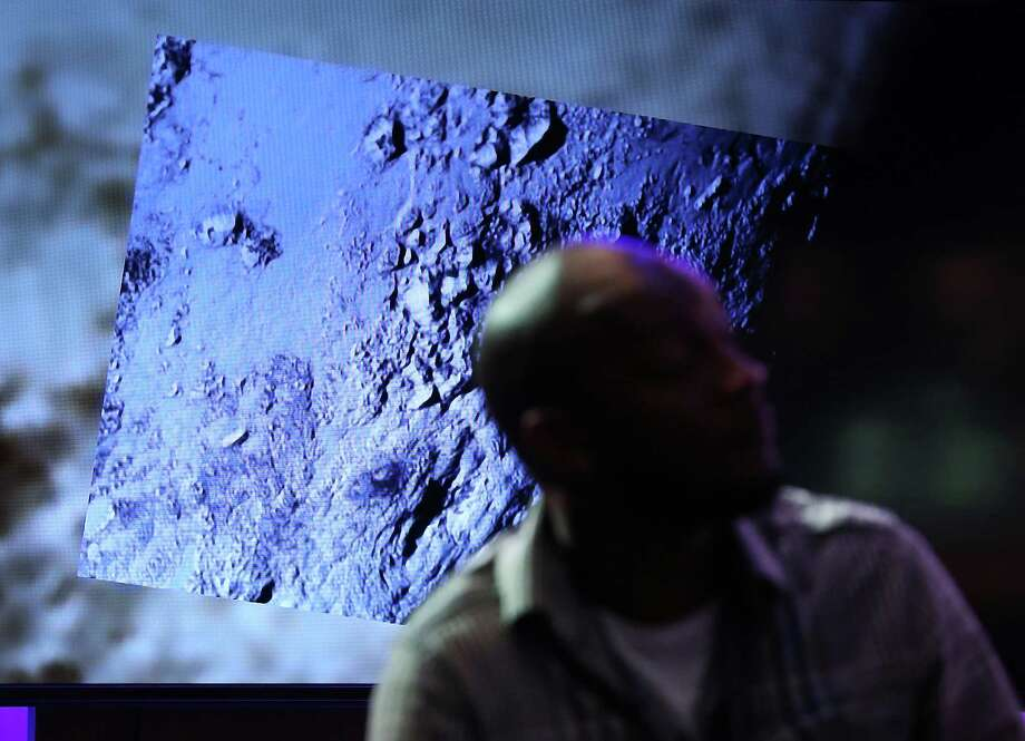 LAUREL, MD - JULY 15: (L-R) The latest image from the New Horizons spacecraft that passed with 7,800 miles of Pluto yesterday, is shown during a NASA news conference July 15, 2015 in Laurel, Maryland. Images from the flyby are being released as they become available. The 1,050-pound piano sized probe, which was launched January 19, 2006 aboard an Atlas V rocket from Cape Canaveral, Florida, zipped by the planet yesterday.  (Photo by Mark Wilson/Getty Images) ORG XMIT: 565074057 Photo: Mark Wilson / 2015 Getty Images