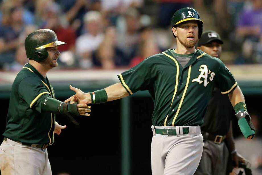 Oakland Athletics' Stephen Vogt, left, and Ben Zobrist celebrate after both scored on an RBI-double by Billy Butler in the eighth inning of a baseball game against the Cleveland Indians, Saturday, July 11, 2015, in Cleveland. (AP Photo/Tony Dejak) ORG XMIT: OHTD113 Photo: Tony Dejak / AP