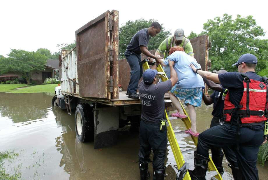 Houston Fire Dept. and other City of Houston personnel help Barbara Levin into a City of Houston dump truck after her house near South Braeswood and Rice was flooded with several feet of water May 26 in Houston flooding.  Photo: Melissa Phillip, Staff / © 2015  Houston Chronicle