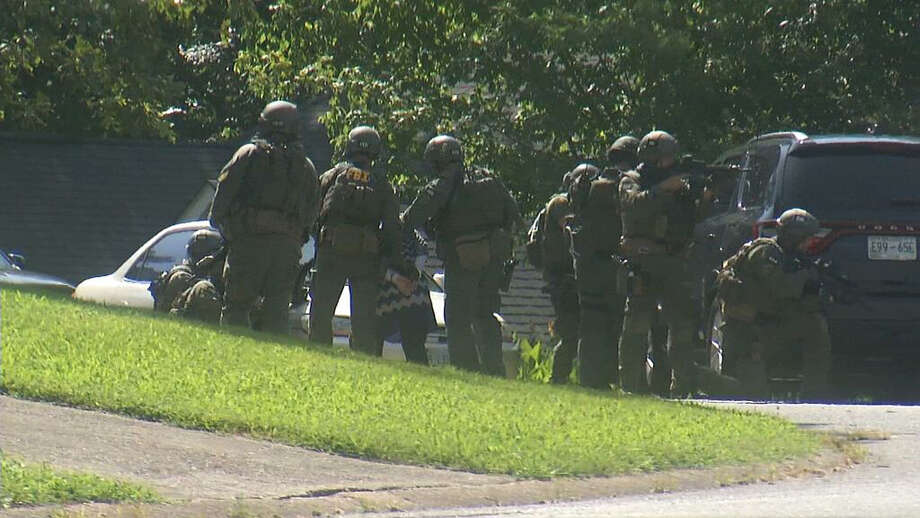 In this frame from video, law enforcement officers detain a woman as they surround a house in Hixson, Tenn., Thursday, July 16, 2015. A gunman unleashed a barrage of fire at two sites a few miles apart in Chattanooga, killing several, officials said. The attacker was also killed. (AP Photo/Alex Sanz) ORG XMIT: NYAG203 Photo: Alex Sanz / AP