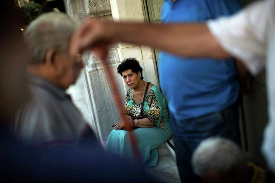 Pensioners wait for the opening of the national bank of Greece to withdraw a maximum of 120 euros ($134) for the week in central Athens, Thursday, July 16, 2015. Greece's troubled left-wing government is seeking urgent relief from European lenders on Thursday, after it pushed a harsh austerity package thought parliament, triggering a revolt in the ruling party and violent demonstrations in central Athens. (AP Photo/Emilio Morenatti) ORG XMIT: EM101 Photo: Emilio Morenatti / AP