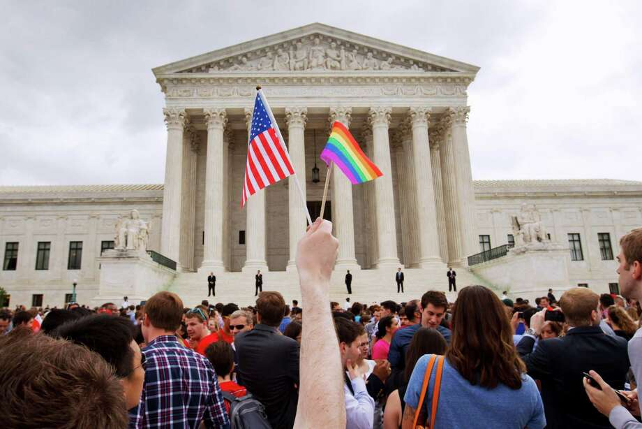 FILE - In this June 26, 2015 file photo, the crowd celebrates outside of the Supreme Court in Washington after the court declared that same-sex couples have a right to marry anywhere in the U.S. A brief exchange during Supreme Court arguments in the same-sex marriage case has exploded into a full-blown crisis for some conservatives who warn that the IRS could start revoking the tax-exempt status of religious groups that oppose gay marriage. The attorneys general of 15 states have written Congress asking for legislation to protect religious schools and other groups. Bills in the House and Senate are gaining support.(AP Photo/Jacquelyn Martin, File) ORG XMIT: WX109 Photo: Jacquelyn Martin / AP