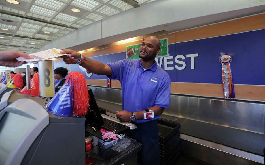Southwest Airlines customer service agent Dee Lacy hands out a boarding pass at Hobby Airport.  The Dallas-based airline is building a $156 million international terminal to open at Houston's Hobby on Oct. 15. Photo: Billy Smith II, Staff / © 2014 Houston Chronicle