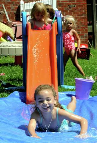 Six-year-old Elise Rodgriguez enjoys her ride down a homemade water slide at the Colonie Community Day Care on Thursday, July 16, 2015, in Colonie, N.Y. (Michael P. Farrell/Times Union) Photo: Michael P. Farrell / 00032648A