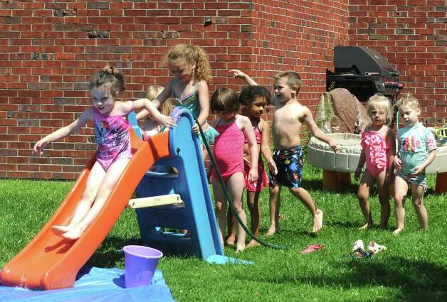 Children enjoy rides down a homemade water slide at the Colonie Community Day Care on Thursday, July 16, 2015, in Colonie, N.Y. (Michael P. Farrell/Times Union) Photo: Michael P. Farrell / 00032648A