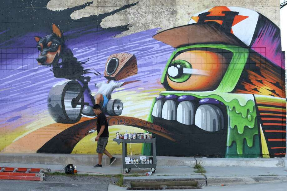 Houston graffiti artist, W3R3ON3 (we are one) finishes a mural outside of KLS Cyclery on the corner of North Main Street and Gargan Street, north of downtown, in July 2015. Photo: Dylan Aguilar, Houston Chronicle / © 2015 Houston Chronicle
