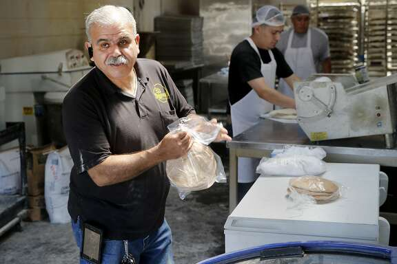 Hamati bakery owner Sam Mizirawi wraps up some wheat pita at his production facility Thursday July 16, 2015. Aroma's Hamati Bakery in San Bruno, Calif. makes homemade breads including pita, zaatar  and sesame rings.