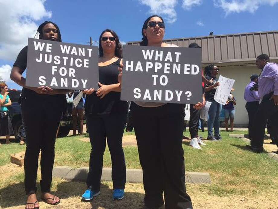 Protesters hold signs outside the Waller County Sheriff's Office on Friday, July 17, 2015. The death of Sandra Bland in police custody has sparked a national attention. Photo: Leah Binkovitz / Houston Chronicle