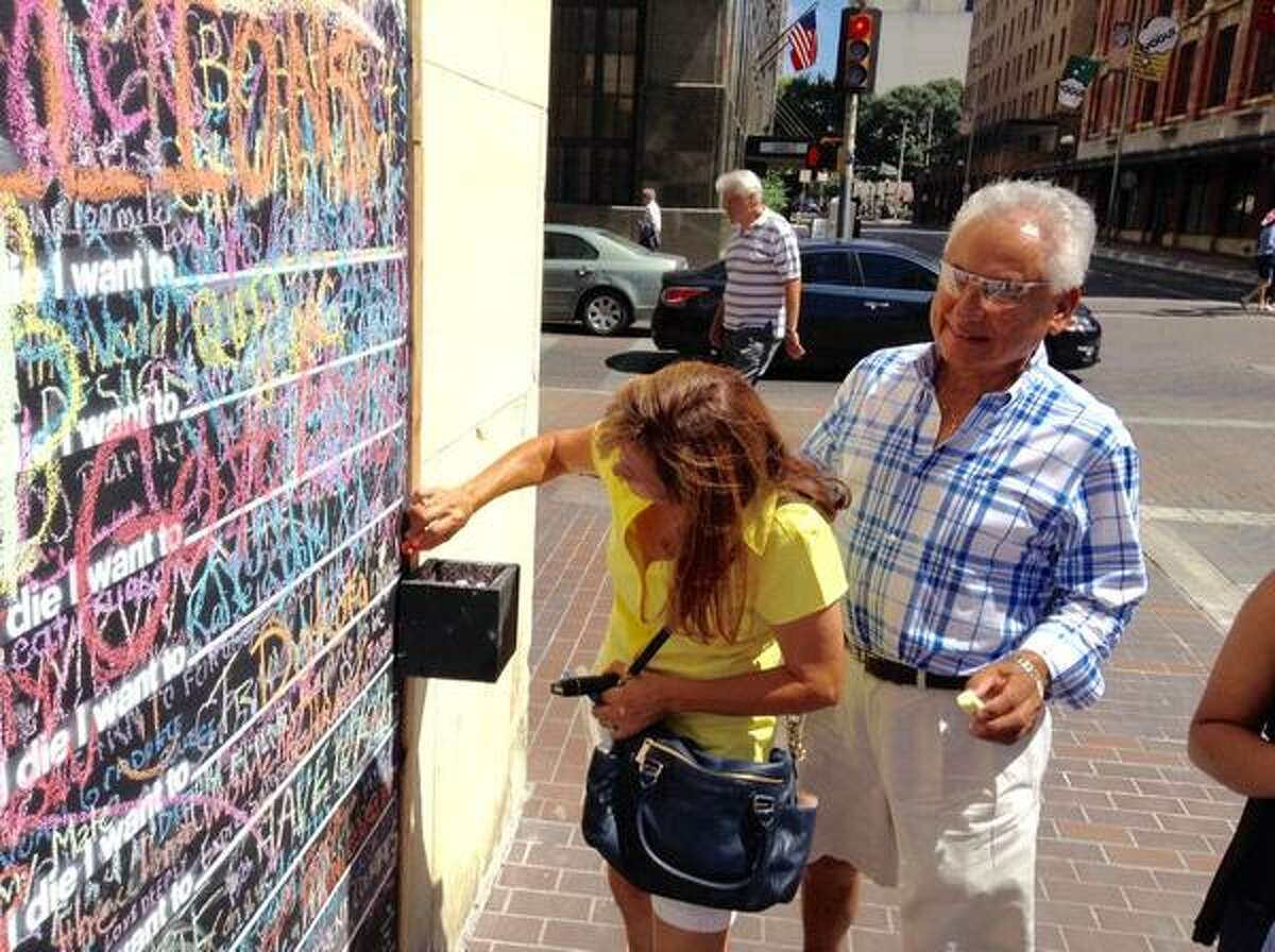 Pete Pruneda watches as his wife Carmen writes on the city's new