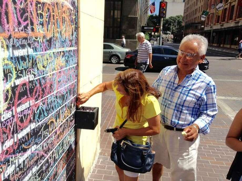 """Pete Pruneda watches as his wife Carmen writes on the city's new """"Before I Die"""" wall at Houston and Navarro streets. Photo: Vincent T. Davis/San Antonio Express-News"""