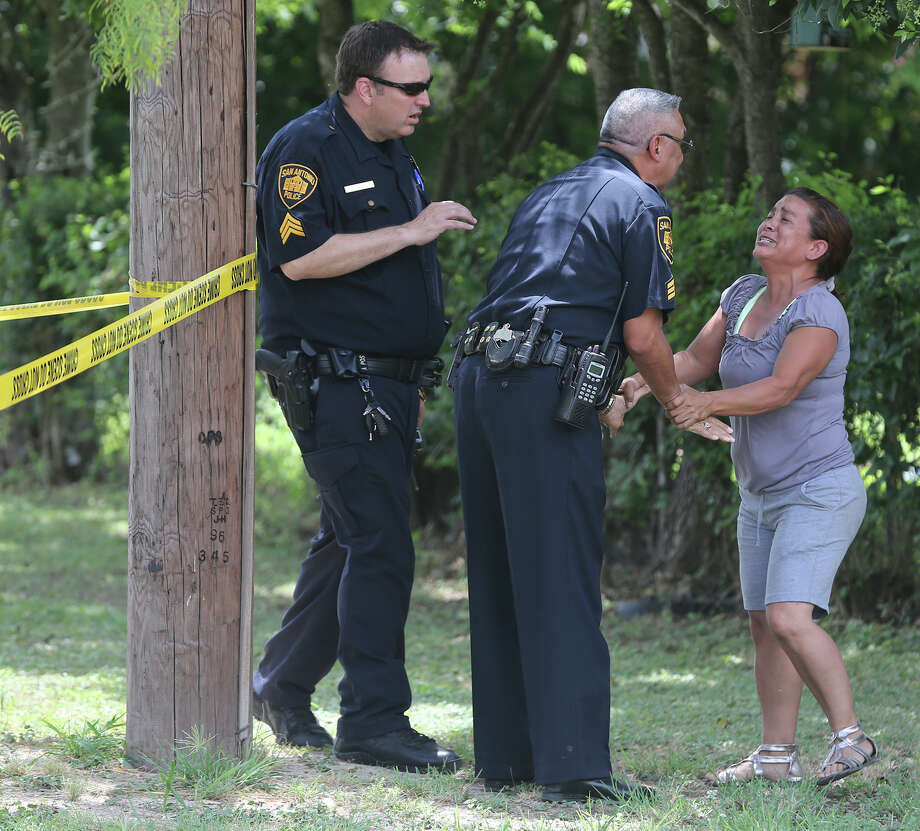 San Antonio police try to calm a grieving woman Friday July 17, 2015 at the scene of a shooting on the 900 block of West Formosa and the city's South Side. The shooting is currently being investigated. The shooting took place about 11:30 a.m.. Photo: John Davenport, San Antonio Express-News / ©San Antonio Express-News/John Davenport