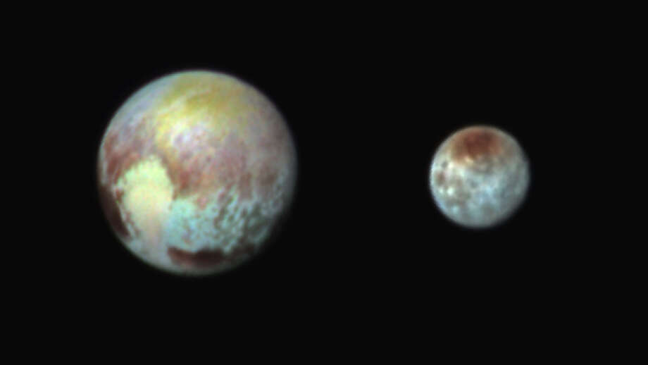 NASA's New Horizons spacecraft captured photos of Pluto, left, and its moon, Charon, with differences in surface material and features depicted in exaggerated colors made by using different filters on a camera aboard the craft. In this composite false-color image, the apparent distance between the two bodies has also been reduced. Photo: /Associated Press / NASA/APL/SwRI