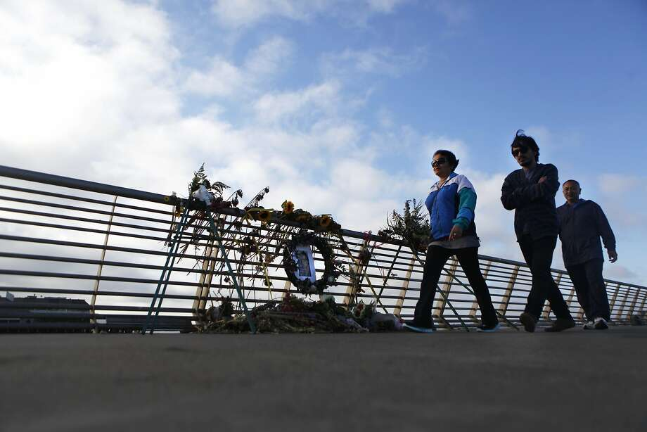 Ashok Karki, Anju Paudel and Apar Karki pass by the Pier 14 memorial for Kathryn Steinle who was fatally shot on July 1 as she walked along the pier with her family. Photo: Cameron Robert, The Chronicle