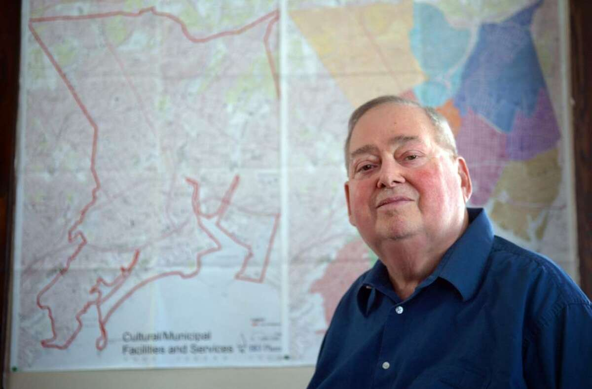 Barry J. Piesner, Chairman of the Bridgeport Business Alliance, poses for a photo in his Bridgeport office with maps of the city behind him.
