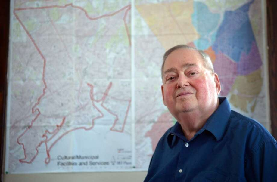 Barry J. Piesner, Chairman of the Bridgeport Business Alliance, poses for a photo in his Bridgeport office with maps of the city behind him. Photo: Autumn Driscoll / Connecticut Post