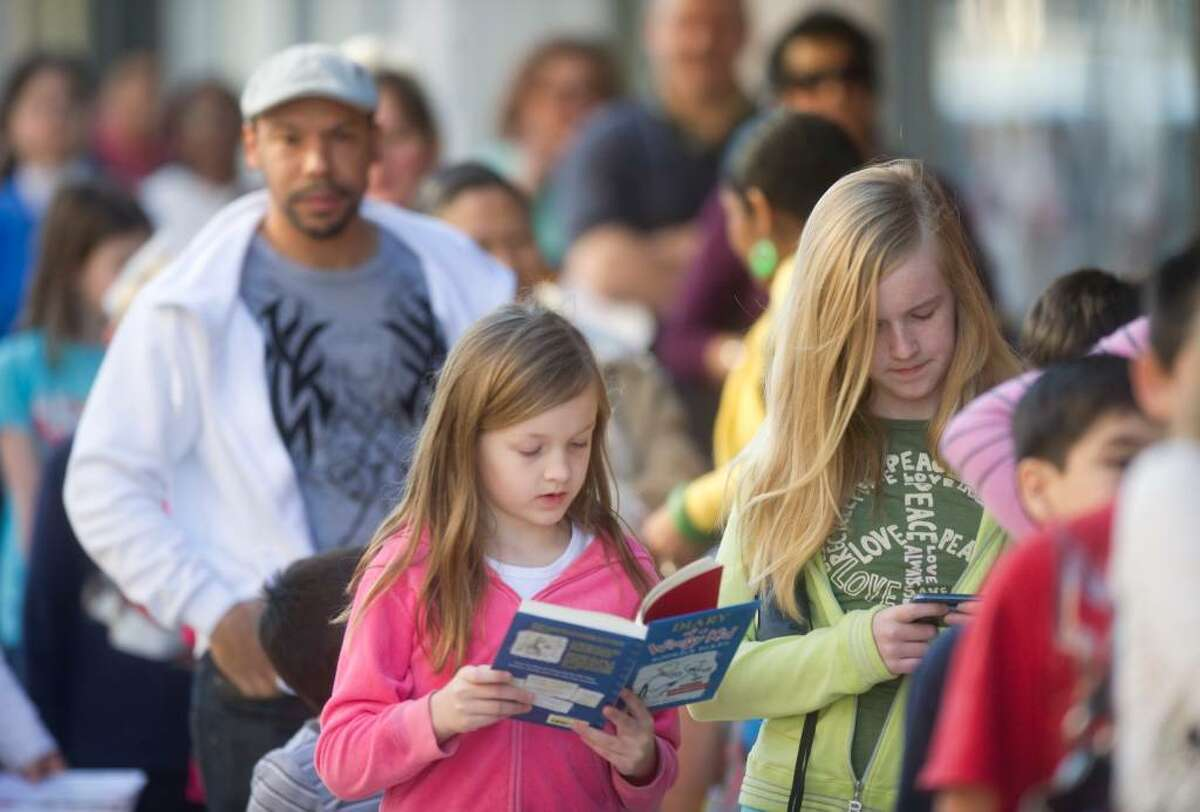 Ella Smith Fitzhugh, 8, reads a Wimpy book, while her sister Emma, 11, uses her cell phone while in line for an event promoting the premiere of Diary of a Wimpy Kid at the Palace Theater in Stamford, Conn. on Wednesday, March 17, 2010.