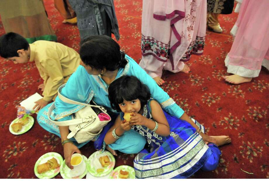 A young girl and her mother eat breakfast after a service to mark the completion of Ramadan Friday, July 17, 2015, at the Muslim Community Center in Colonie, N.Y. (Phoebe Sheehan/Special to The Times Union) Photo: PS / 00032617A
