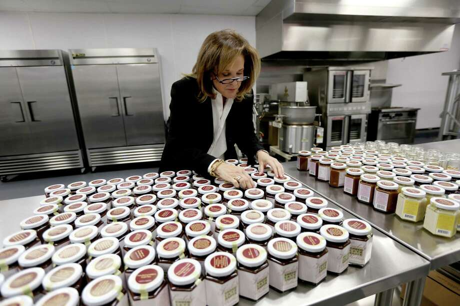 Lynn Lasher, founder of Somebody's Mother's Chocolate Sauce, looks over jars at her new facility in Houston. Each jar of Somebody's Mother's displays a quote about mothers or a quote from a famous mother on its lid. Photo: Gary Coronado, Staff / © 2015 Houston Chronicle