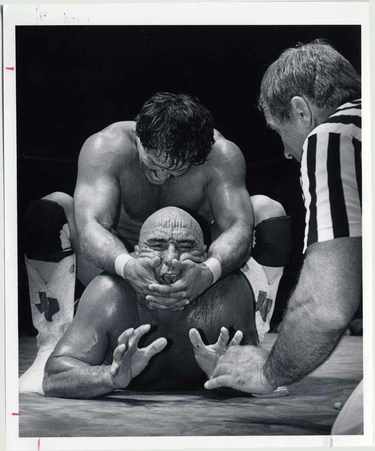 Cowboy Scott Casey puts a head lock on the Mongolian Stomper at Sam Houston Coliseum in 1982. File photo Photo: Betty Tichich, HP Staff / Houston Post files