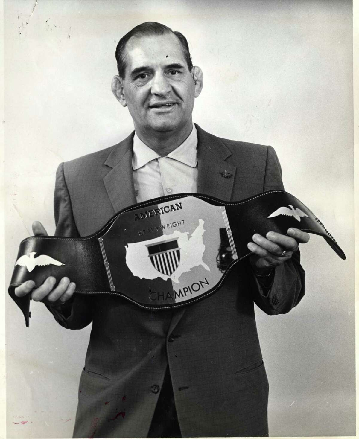 In 1962, Paul Boesch holds a wrestling title belt with American Heavyweight Champion on the buckle.