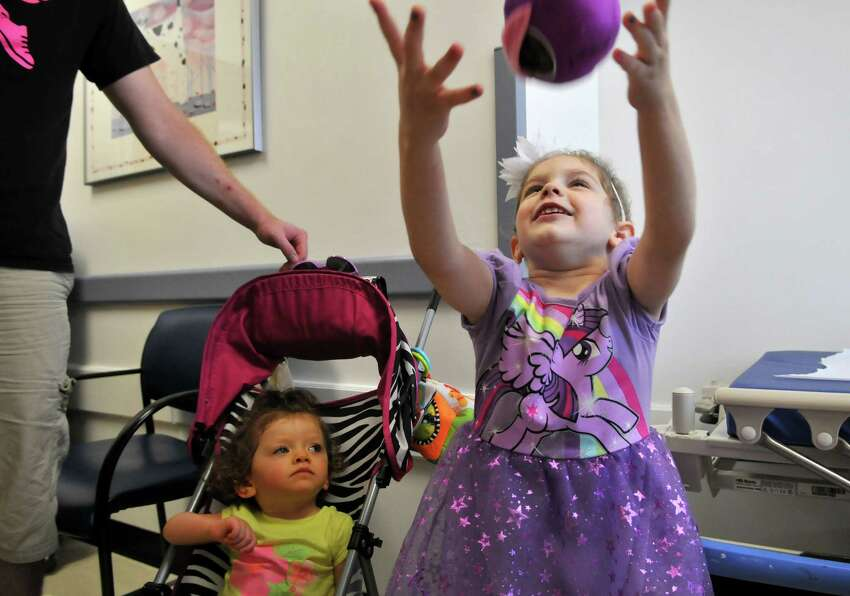 Abby Sayles, right, plays with her stuffed animal she calls