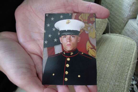 Caroline Dove holds a photo of Marine Corps Lance Cpl. Skip Wells, her boyfriend, in her hands July 17, 2015, at her home in Savannah, Ga. Wells was among four Marines killed July 16, 2015, in an attack at a military training facility in Chattanooga, Tenn. Muhammad Youssef Abdulazeez opened fire Thursday, July 16, 2015, on two U.S. military sites in Chattanooga in an attack that left four Marines dead and raised the specter of terrorism on U.S. soil. He was killed by police.(AP Photo/Russ Bynum)