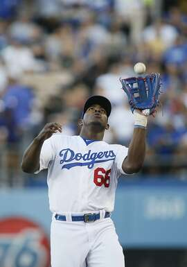 Los Angeles Dodgers right fielder Yasiel Puig catches a foul ball ball hit by Milwaukee Brewers' Jean Segura during the second inning of a baseball game, Saturday, July 11, 2015, in Los Angeles. (AP Photo/Danny Moloshok)