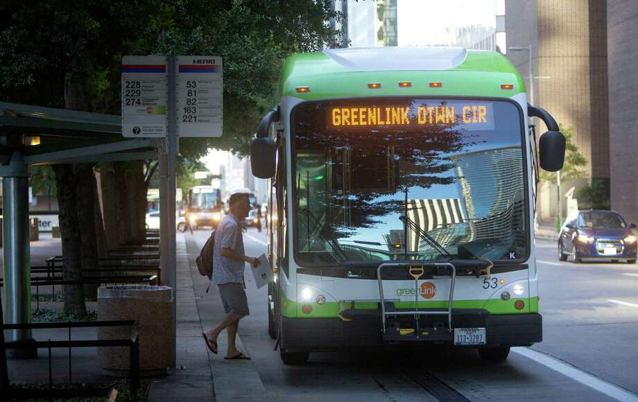 A passenger boards a GreenLink bus July 17 along Smith Street. Many use the buses for short hops around the downtown Houston area. Photo: Cody Duty, Houston Chronicle / © 2015 Houston Chronicle