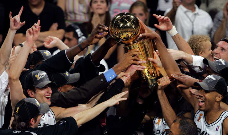 Spurs reach out to touch the Larry O'Brien NBA championship trophy during presentation following their Game 7 81-74 win over the Detroit Pistons in the NBA Finals at the SBC Center on June 23, 2005 .
