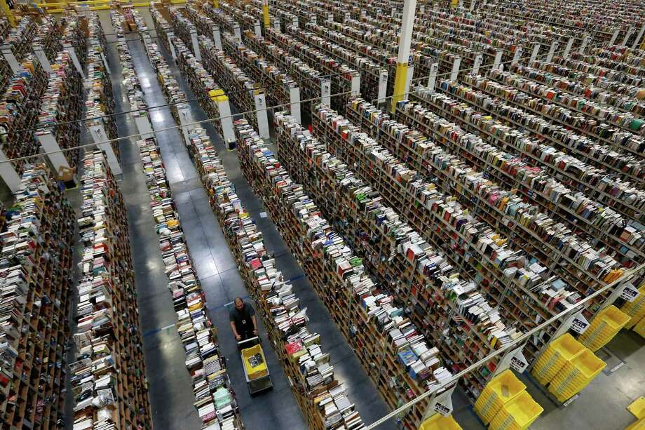 An Amazon employee walks down one of the miles of aisles at the company's fulfillment center in Phoenix. Amazon launched at the dawn of the Web as an online bookseller on July 16, 1995. Photo: Associated Press File Photo / AP