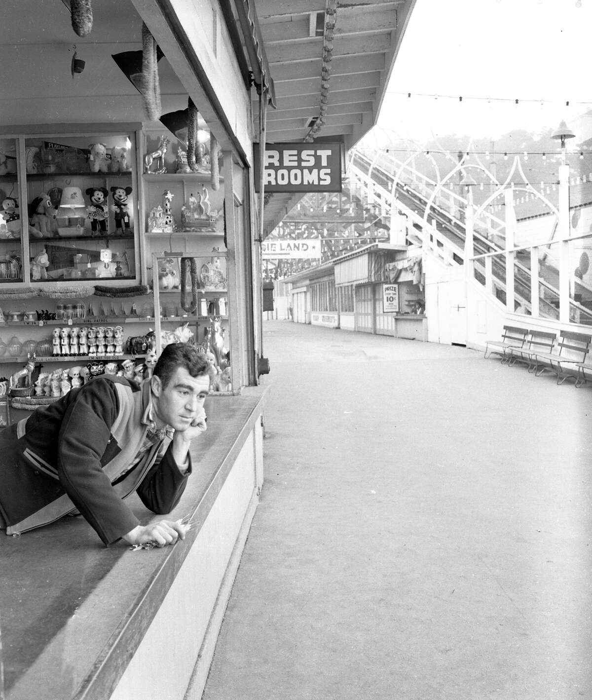 Top: Sutro Baths, which opened next to the Cliff House in 1896, burns during a fire in 1966. Above: Bob Michelson, at a Playland midway concession, waits for customers in 1949.