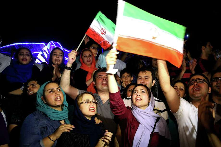 Jubilant Iranians sing and wave Iran flags during street celebrations following a landmark nuclear deal, in Tehran, Iran, July 14, 2015.  (AP Photo/Ebrahim Noroozi) Photo: Ebrahim Noroozi, STR / AP