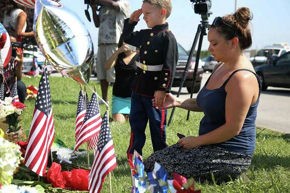 Blake Miller and his mother, Ashley, whose husband is a lieutenant in the Marine Corps, pay their respects Friday to those killed by a gunman in Chattanooga, Tenn., at the Armed Forces Career Center/National Guard Recruitment Office. Four Marines were slain.