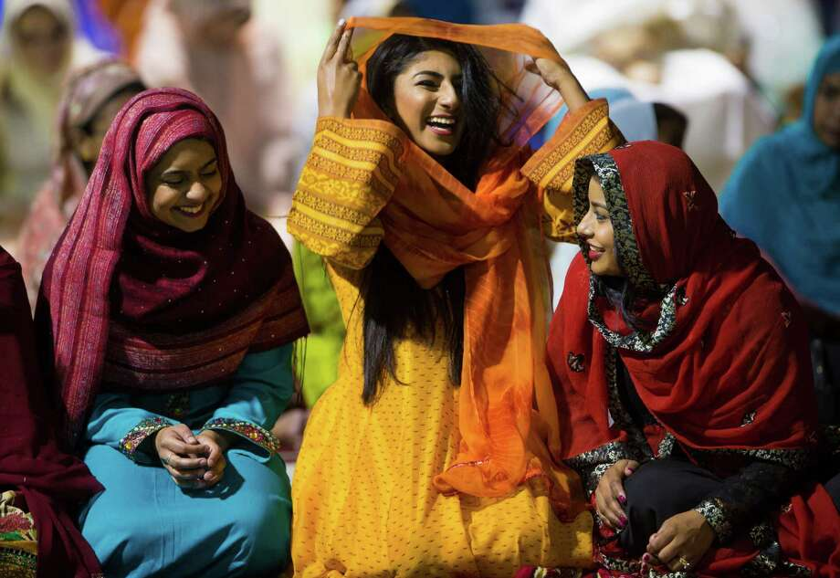 Mediha Zahir, from left, Kanza Khan and Nidha Halepota share a few laughs Friday after the Eid-ul-Fitr prayer at NGR Arena. Photo: Marie D. De Jesus, Staff / © 2015 Houston Chronicle